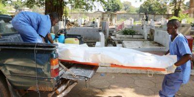 Des membres d'un personnel médical de la croix-rouge en train de transporter un corps