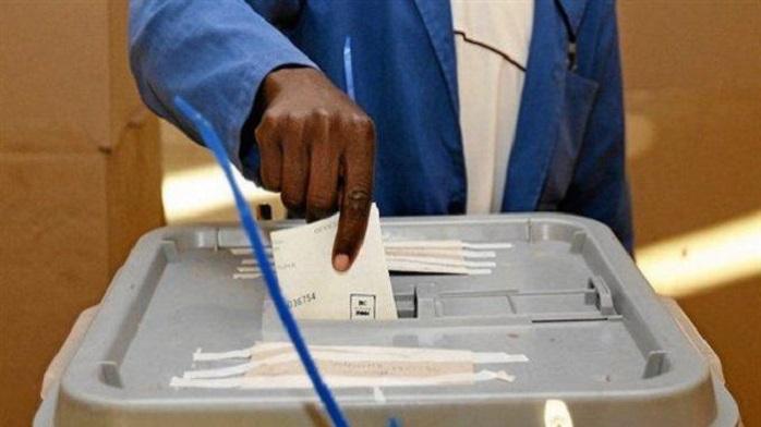 Un homme en train de glisser son bulletin dans l'urne