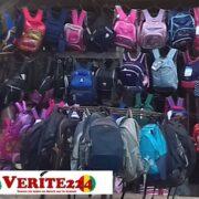 Des sacs scolaires étalés par un vendeur qui affirme qu'il y a eu une hausse du prix des fournitures scolaires