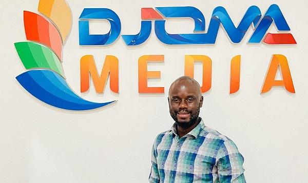Le journaliste Robbie Sarah devant l'insigne de Djoma Media