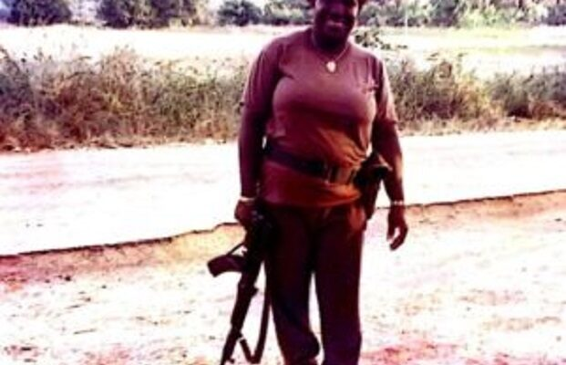 Lieutenant-colonel Manou Cissé tenant une arme à la main