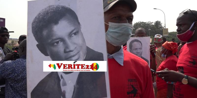 Un enfant d'une victime tenant le portrait de son père lors de la commémoration de la première pendaison du régime de Sékou Touré