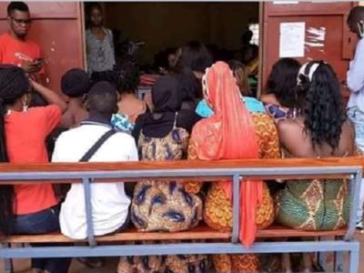 Des étudiants assis en dehors de classe pour suivre des cours dans une salle remplie