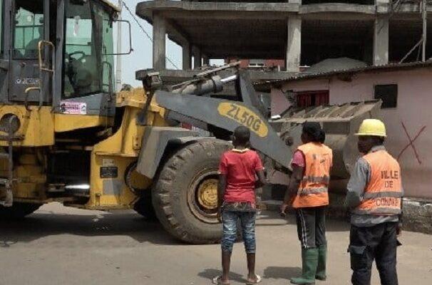 Un bulldozer en pleine action en train de déguerpir des emprises au bord de la route (image d'illustration)
