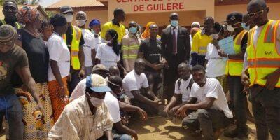 Photo de famille devant le centre de couture de Guiléré offert par l'Alliance minière responsable (AMR)